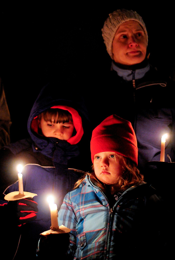 A family holds candles during a vigil in remembrance of the Newtown shooting victims at Green Lake Park on Saturday, December 15, 2012. Yesterday Adam Lanza killed his mother, a substitute teacher at Sandy Hook Elementary, before heading to the school and killing 26 adults and children. Lanza shot himself afterwards, bringing the final death toll to 28 people. (Photo by Lindsey Wasson)