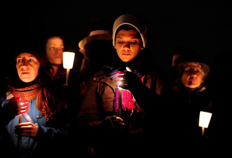 People shield their candles from the wind and light rain during a candlelight vigil in remembrance of the Newtown shooting victims at Green Lake Park in Seattle on Saturday, December 15, 2012. Yesterday Adam Lanza killed his mother, a substitute teacher at Sandy Hook Elementary, before heading to the school and killing 26 adults and children. Lanza shot himself afterwards, bringing the final death toll to 28 people. (Photo by Lindsey Wasson)